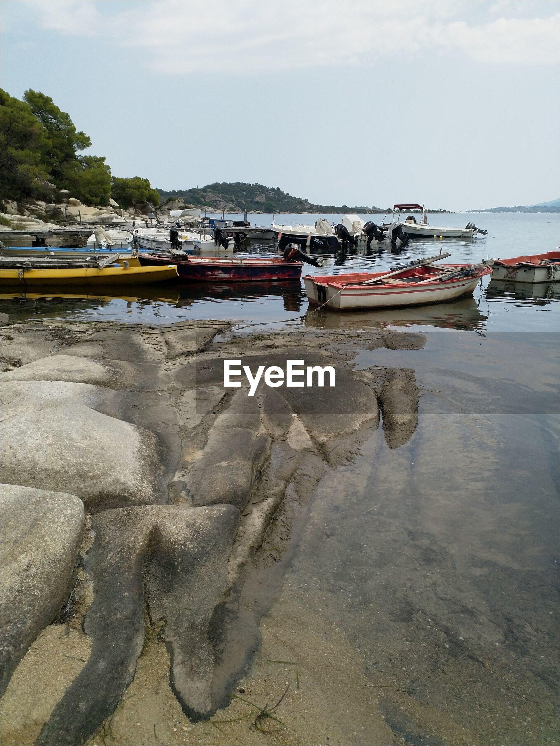 BOATS MOORED ON SEA SHORE AGAINST SKY