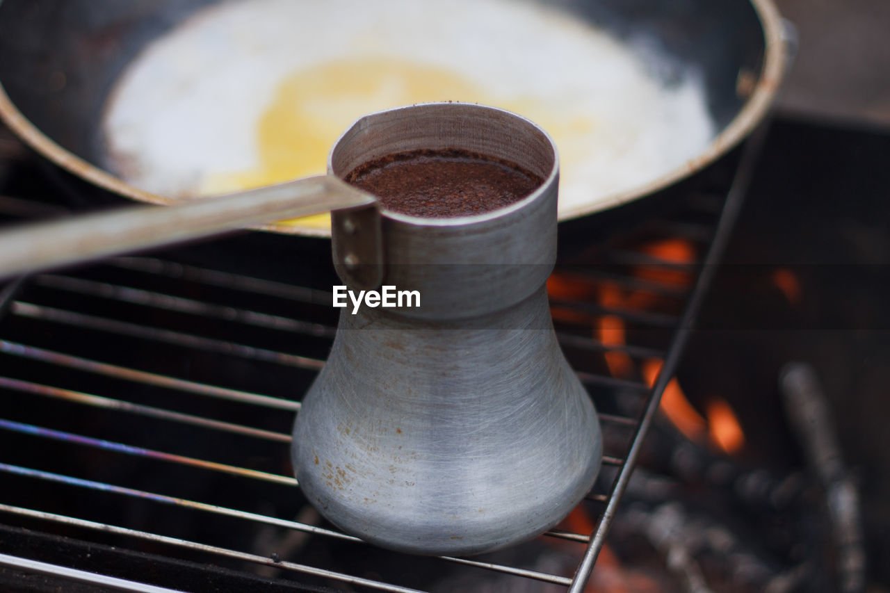 Close-Up Of Ladle Over Grill