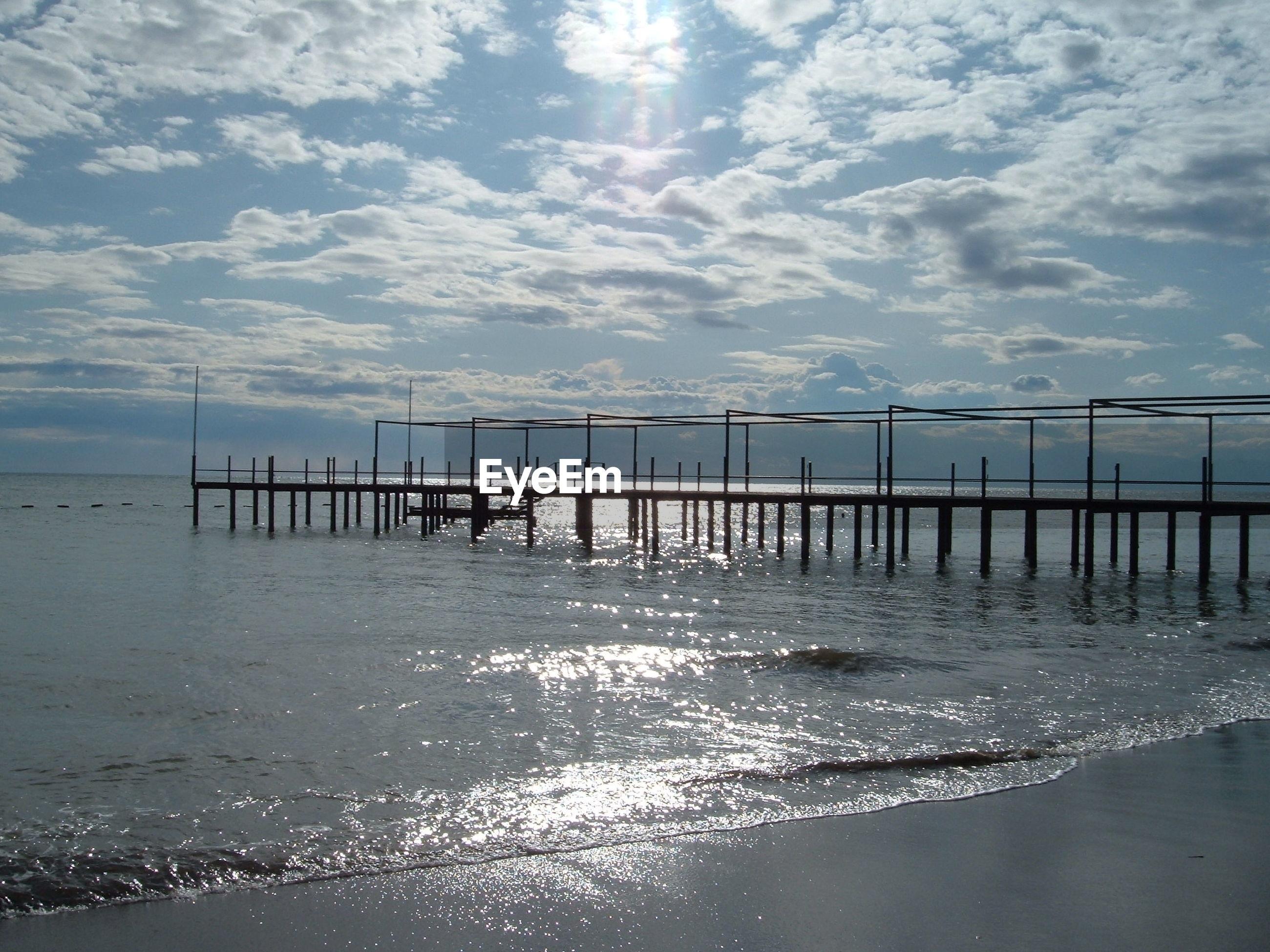Pier at beach against cloudy sky on sunny day