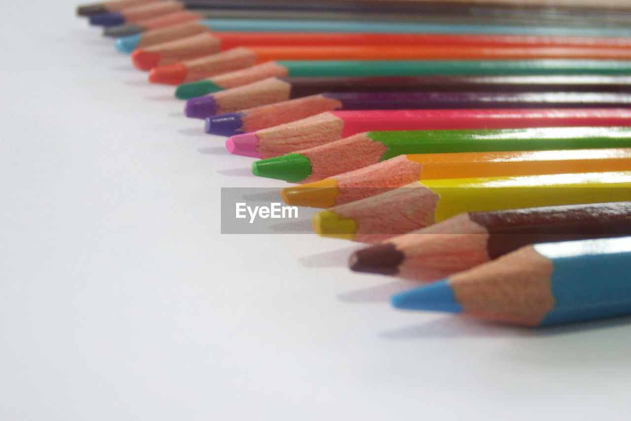 CLOSE-UP OF COLORED PENCILS ON WHITE TABLE
