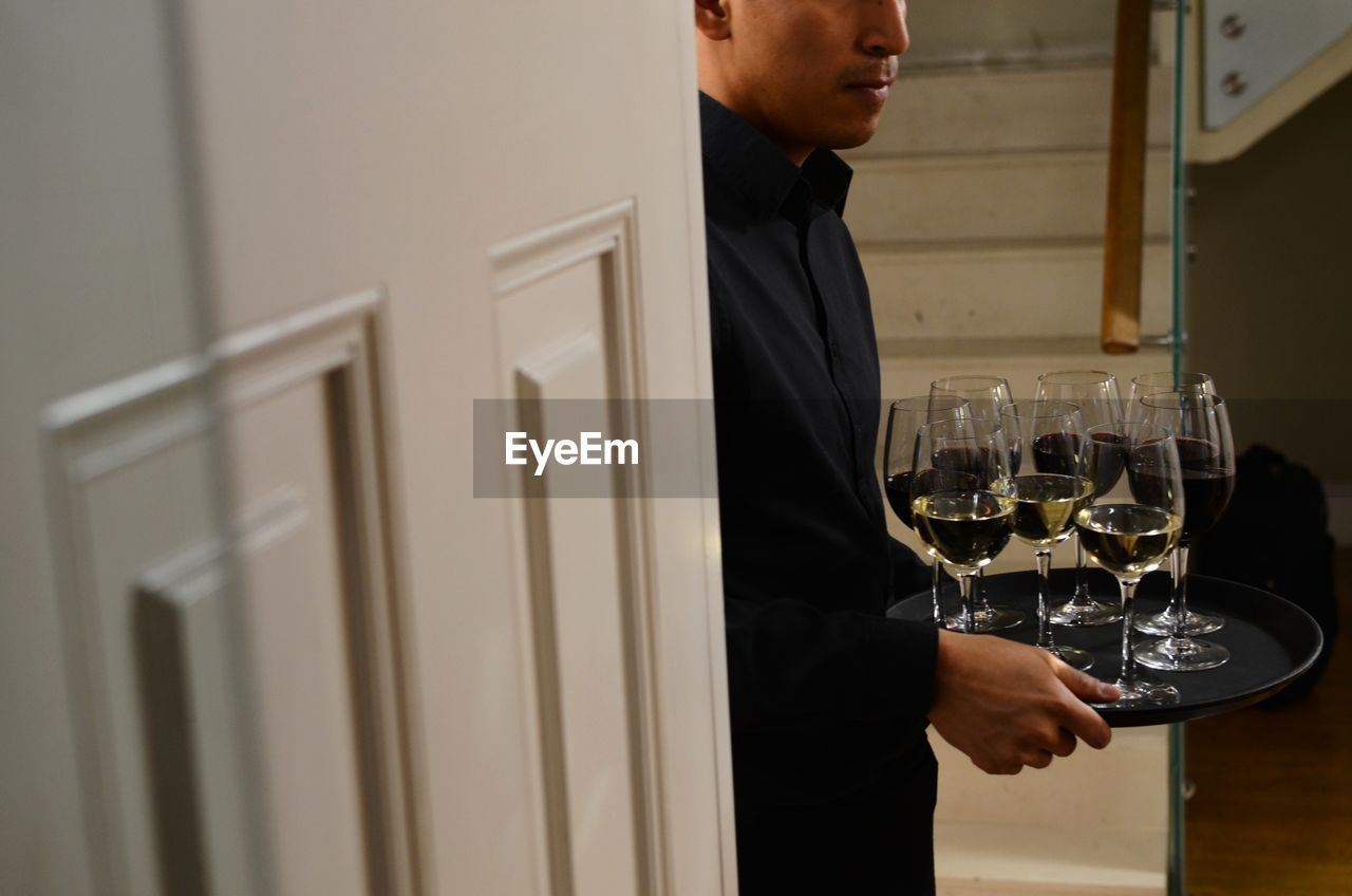 refreshment, glass, drink, alcohol, real people, one person, food and drink, wineglass, wine, indoors, standing, lifestyles, men, young adult, glass - material, holding, leisure activity, business, occupation
