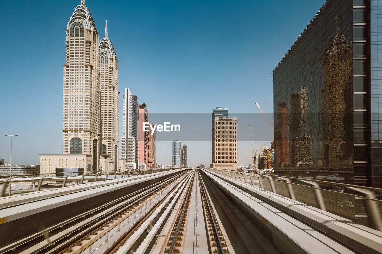 Railroad tracks by buildings against clear sky