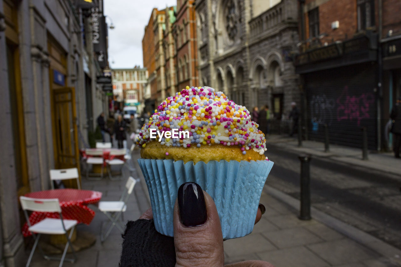 Close-Up Of Hand Holding Cupcake Against Buildings