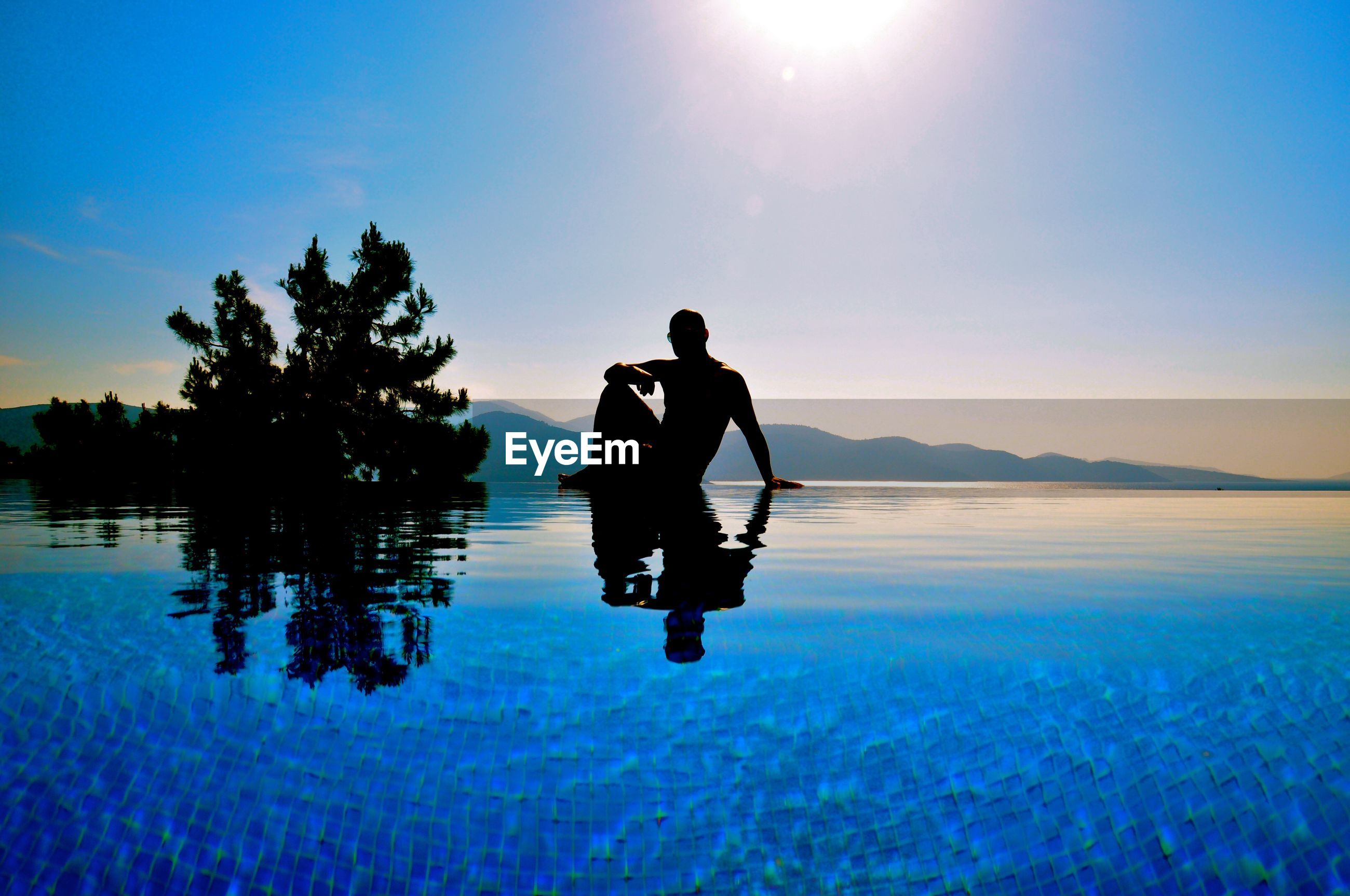 Silhouette man sitting at infinity pool against sky on sunny day