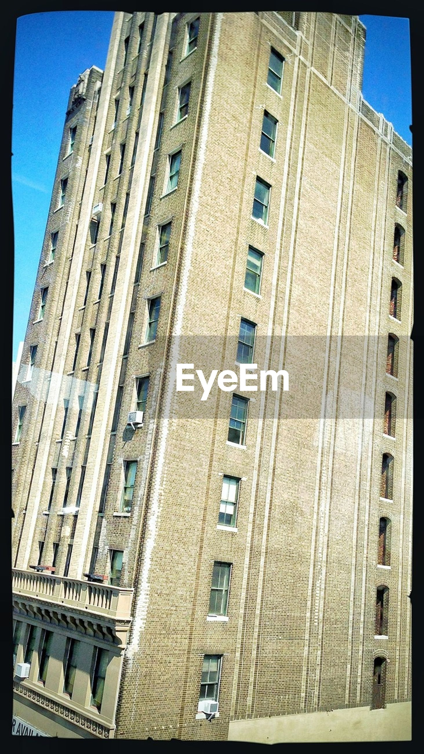 architecture, building exterior, built structure, transfer print, low angle view, city, auto post production filter, building, residential building, residential structure, window, day, balcony, city life, outdoors, apartment, in a row, clear sky, sunlight, sky