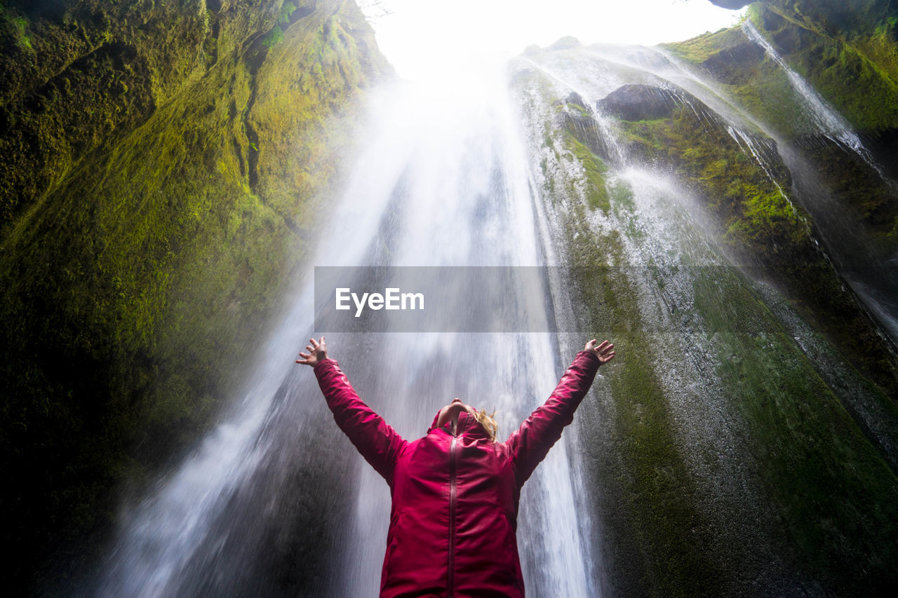Low Angle View Of Mid Adult Woman With Arms Raised Standing Against Waterfall