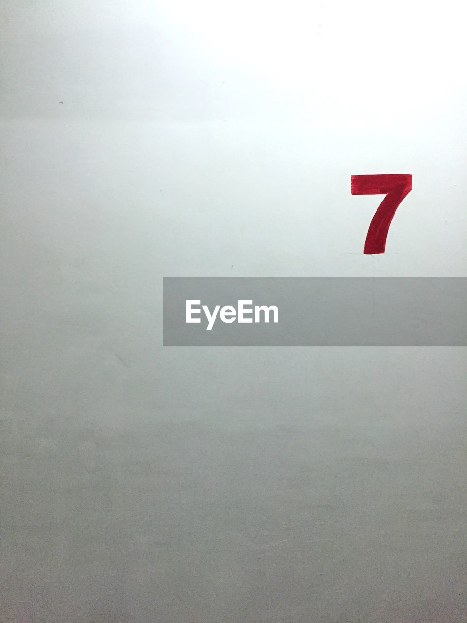 Close-up of number 7 painted on white wall
