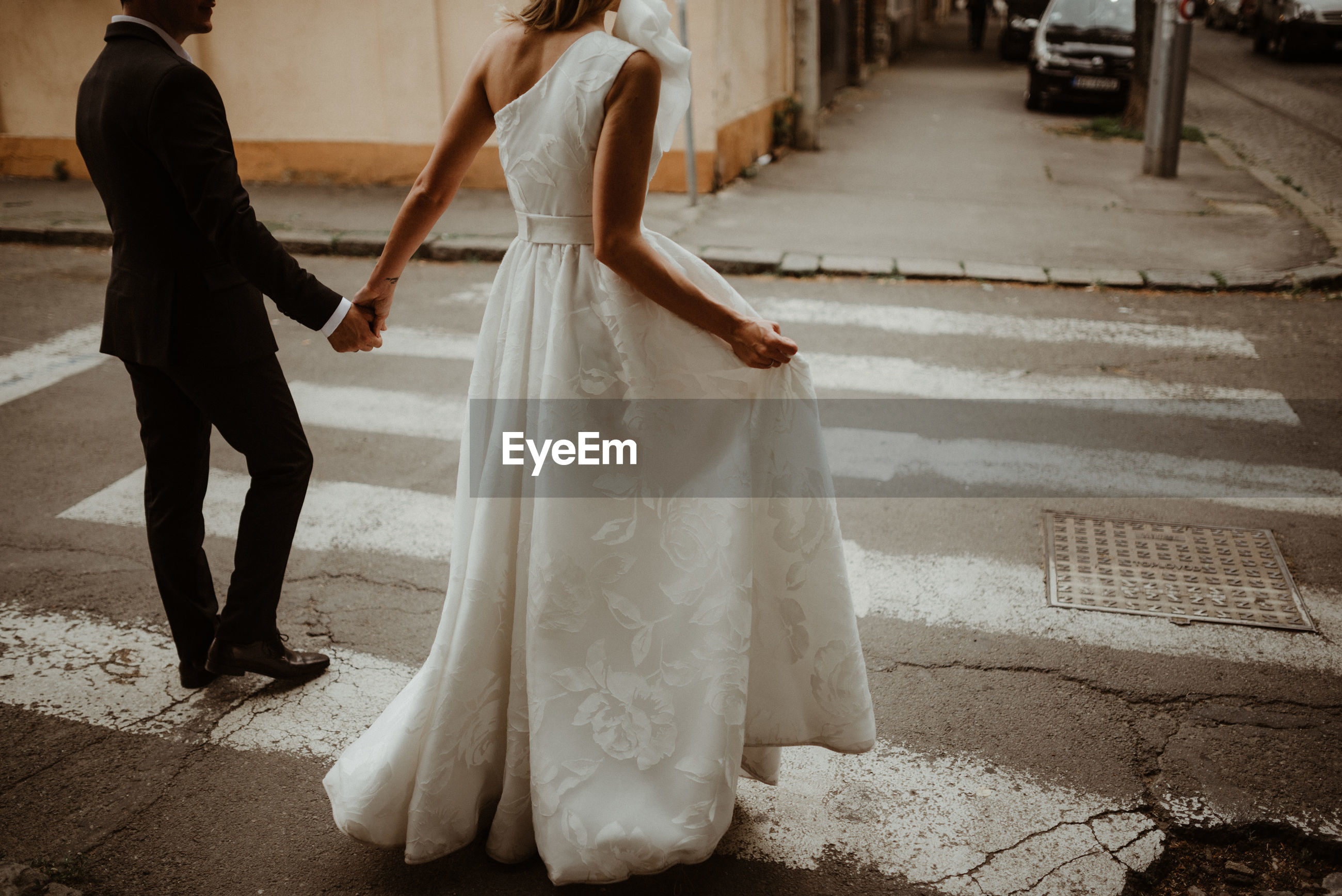 Low section of bride and bridegroom holding hands while crossing road