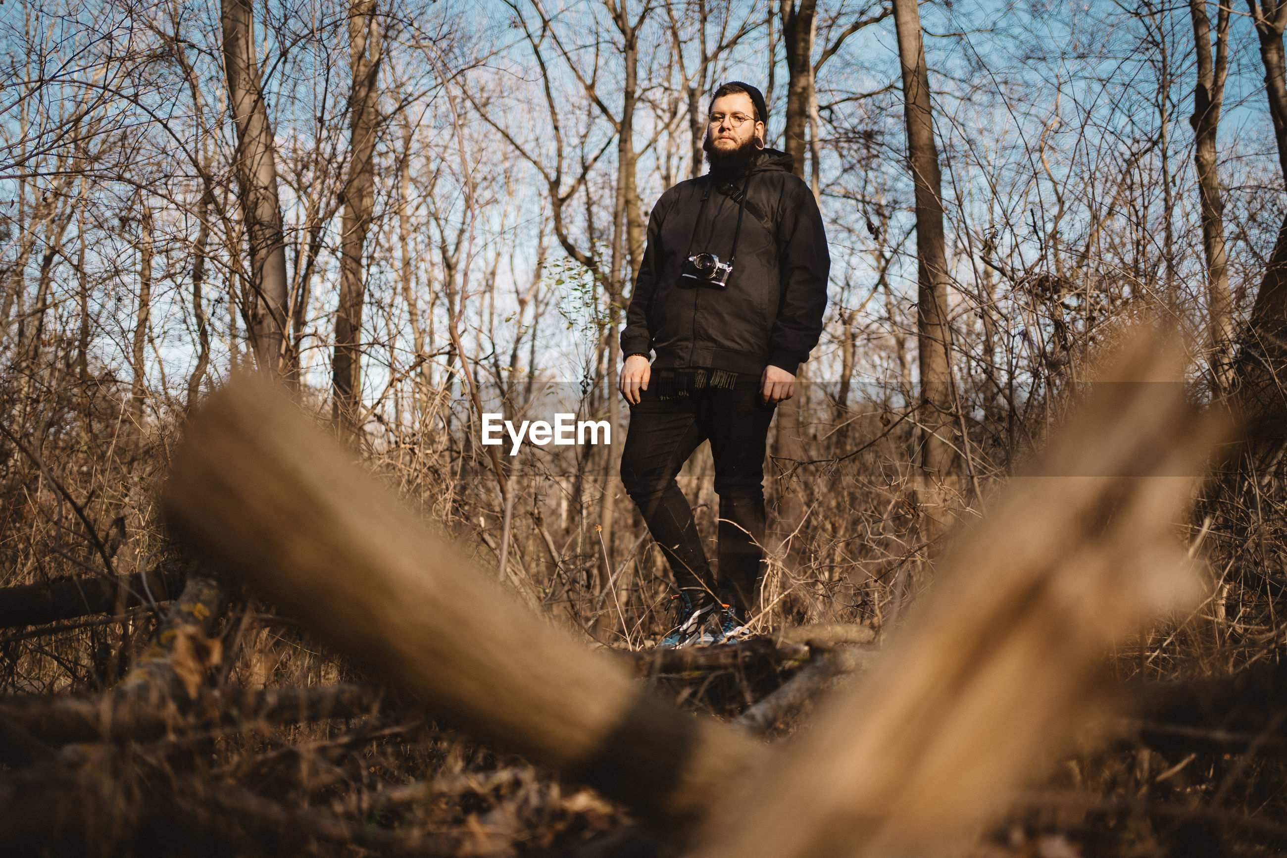 A young bearded man posing in an all black casual outfit on a tree trunk