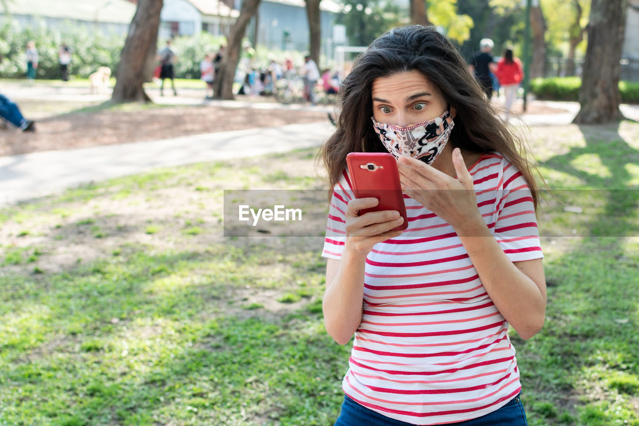 Shocked woman with mask looking at mobile phone while standing in park
