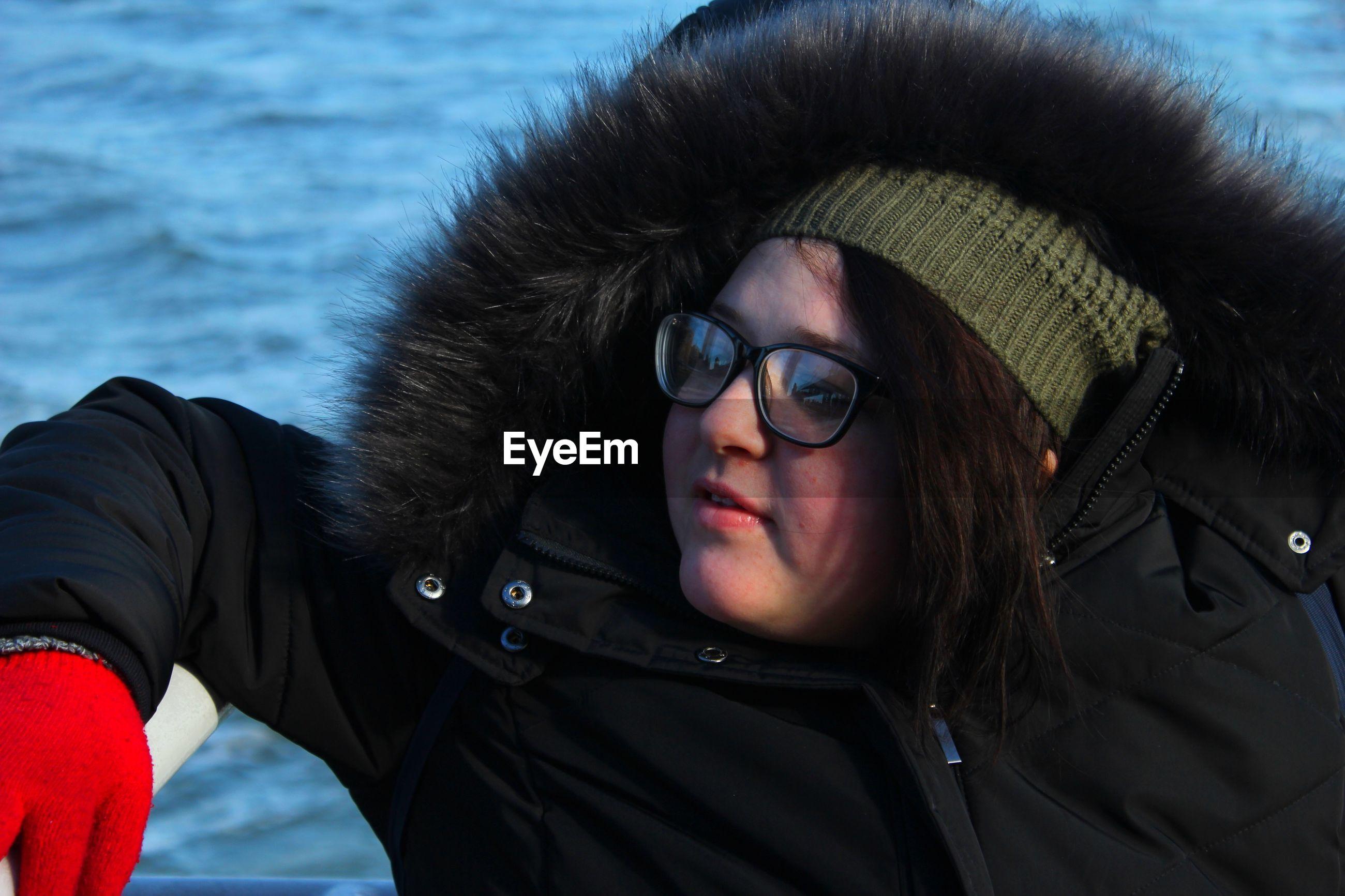 Woman wearing fur coat looking away while sitting against sea