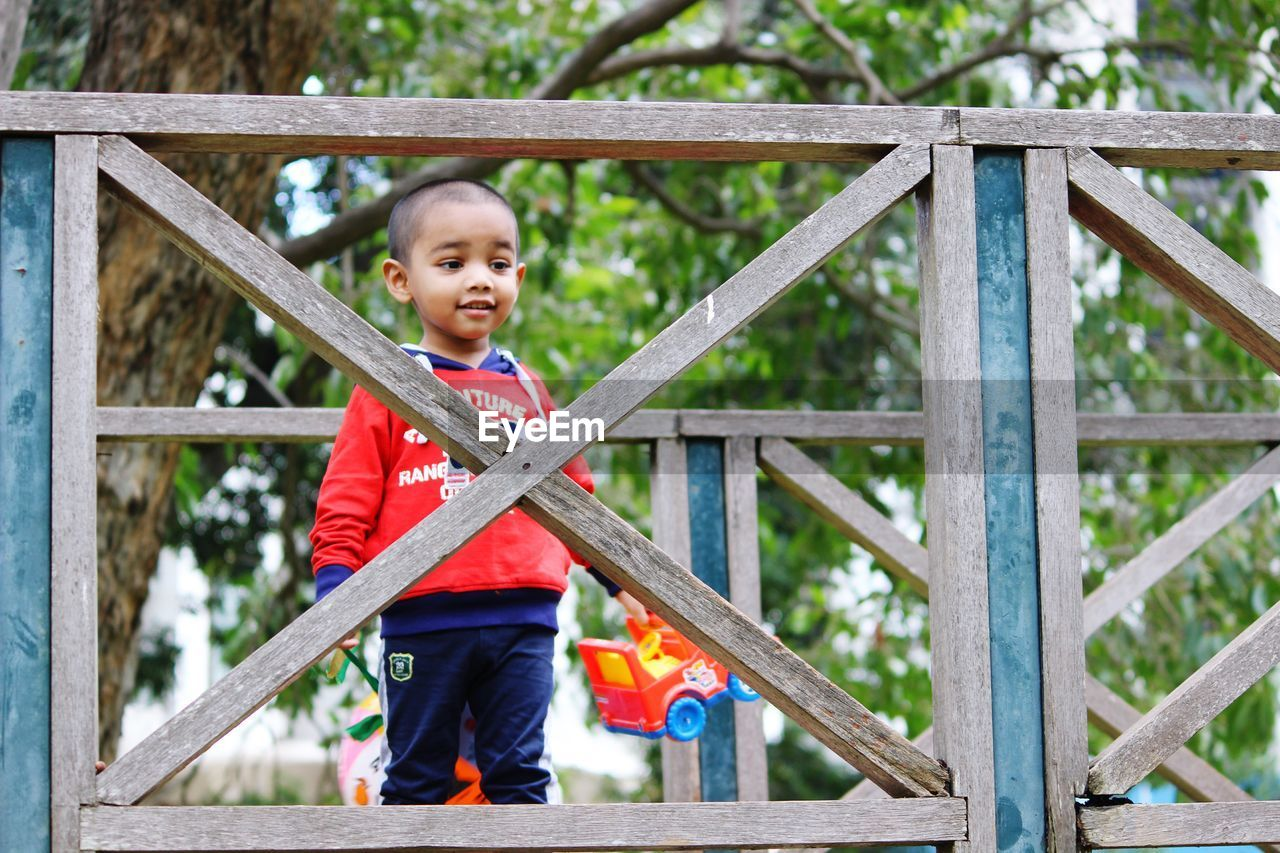 Low Angle View Of Boy Standing On Footbridge At Playground