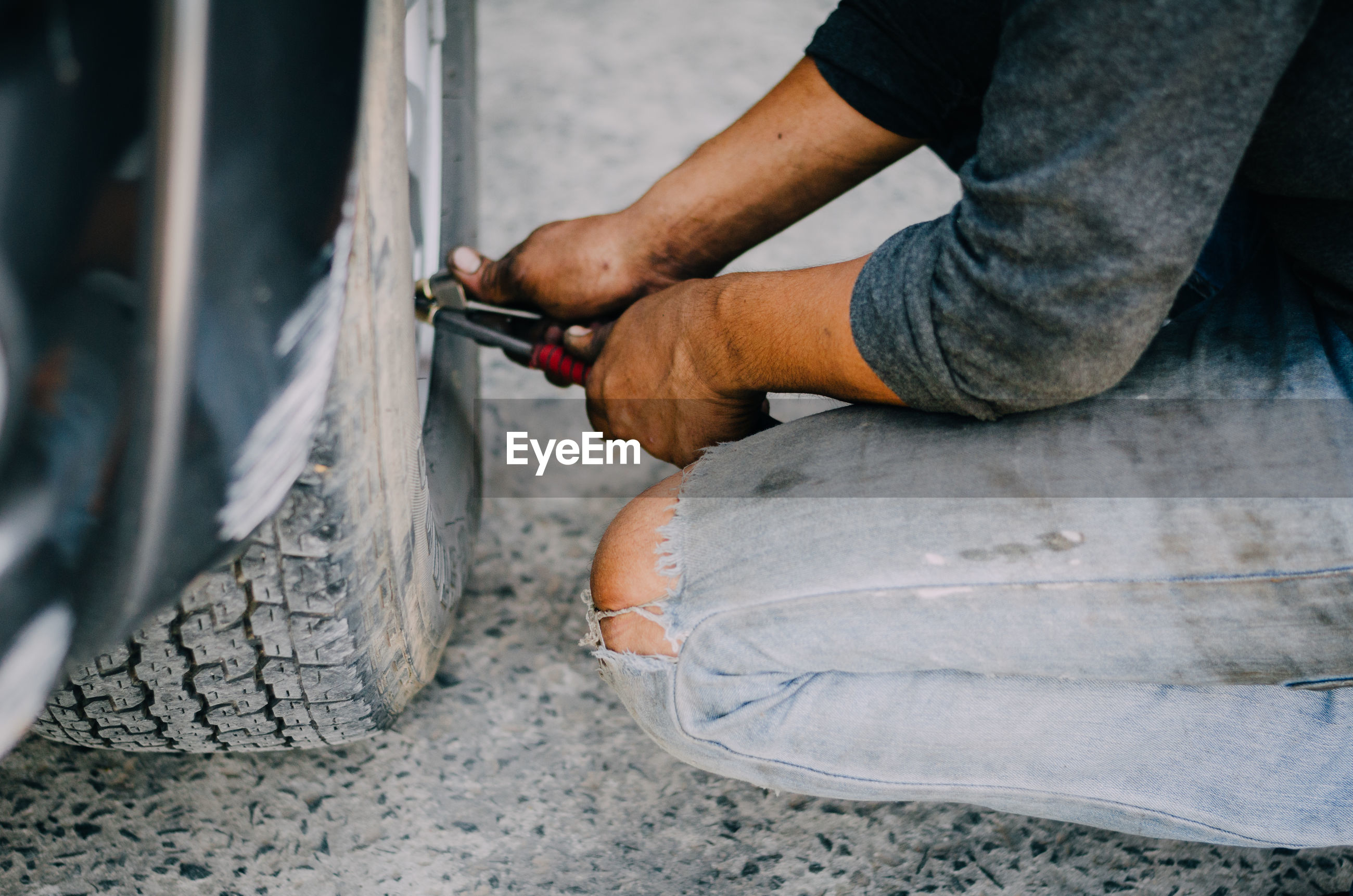 Cropped image of male mechanic repairing car tire