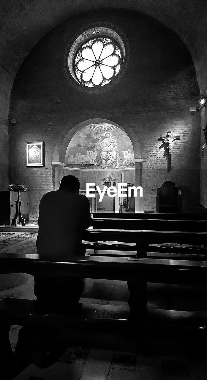 indoors, religion, arch, spirituality, place of worship, pew, rear view, real people, window, altar, sitting, men, architecture, built structure, one person, day, people