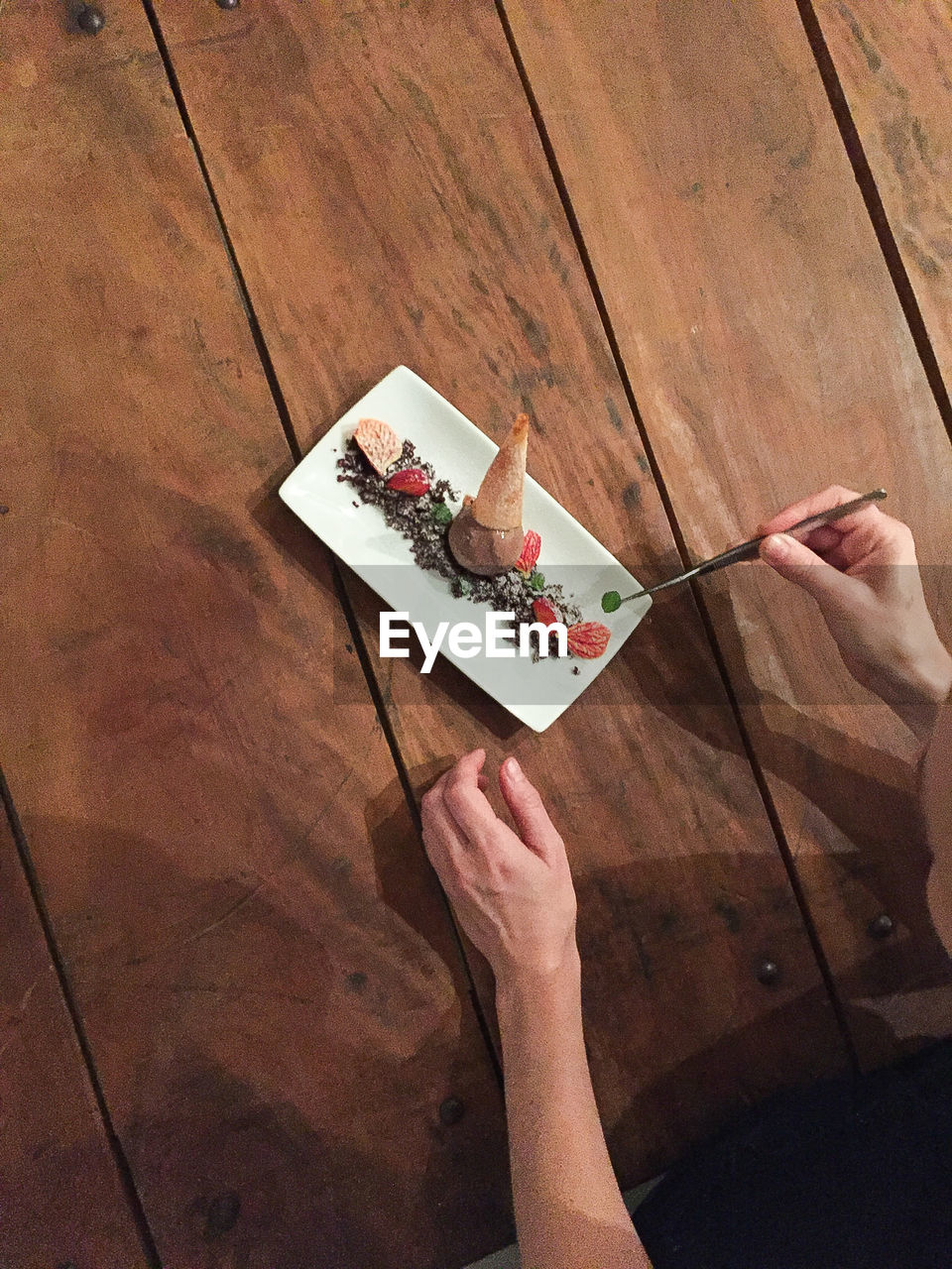 Cropped Image Of Chef Preparing Dessert In Plate On Table