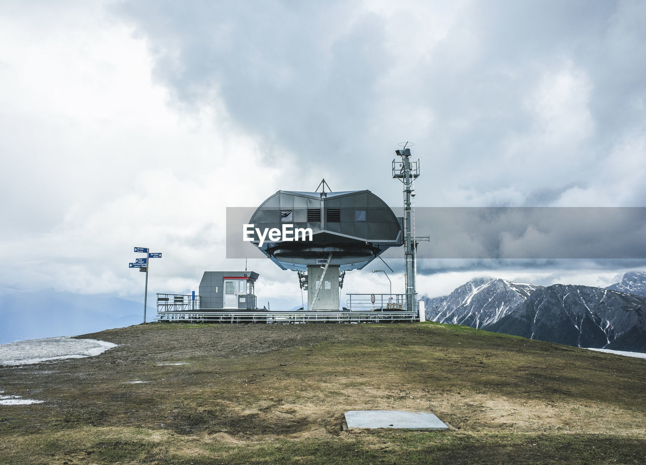 Ski lift station and mountains against cloudy sky