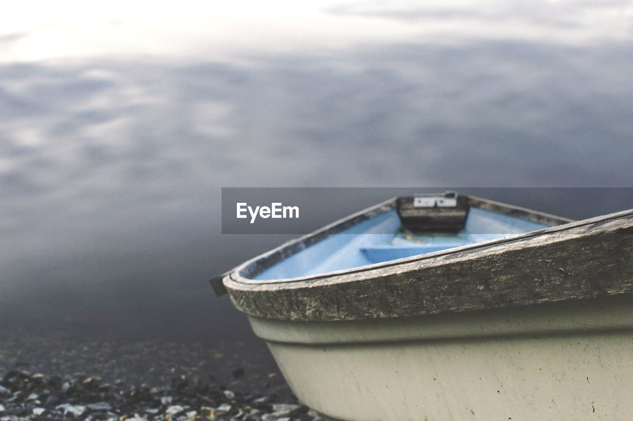 nautical vessel, water, day, focus on foreground, no people, nature, transportation, mode of transportation, outdoors, close-up, moored, beach, lake, metal, cloud - sky, selective focus, sky, travel, land, rowboat, steel