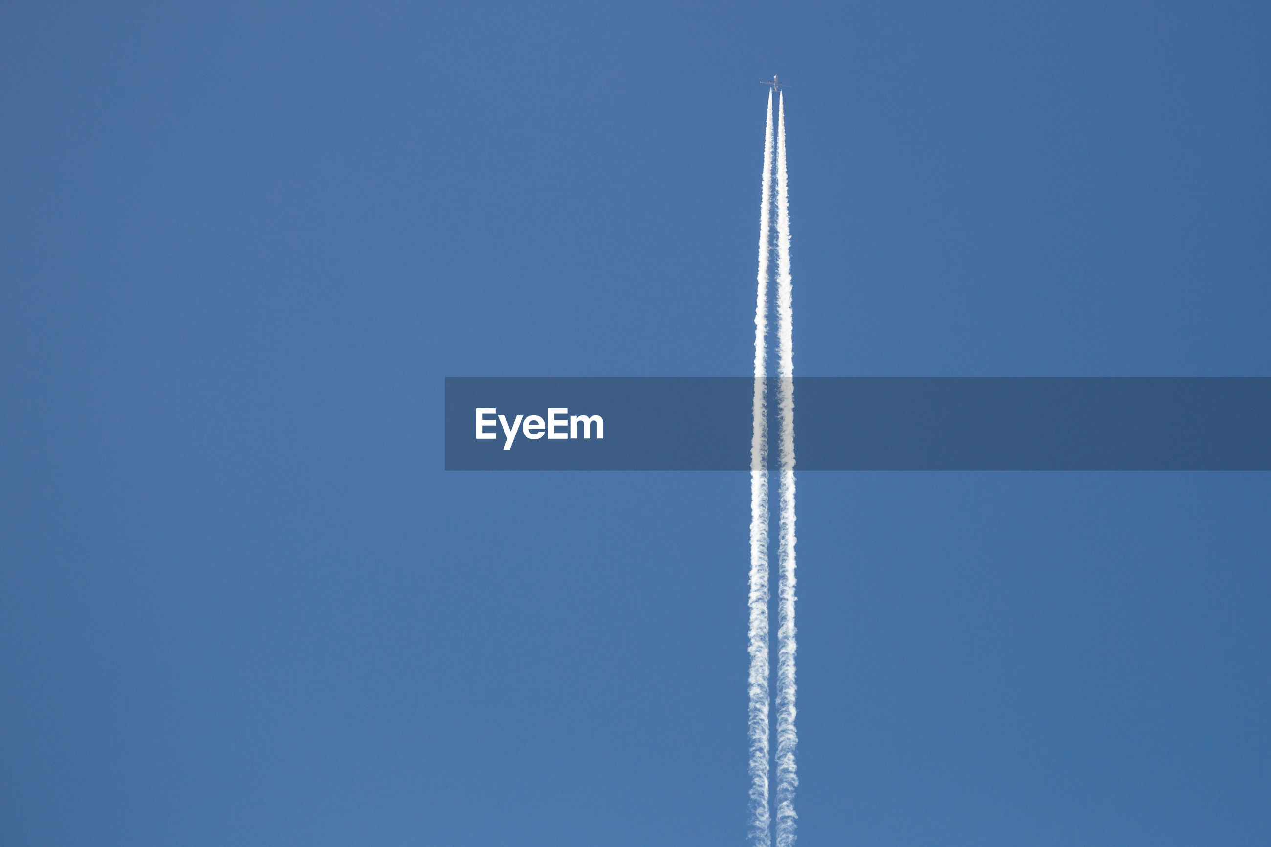 Low angle view of aircraft vapor trail against clear blue sky