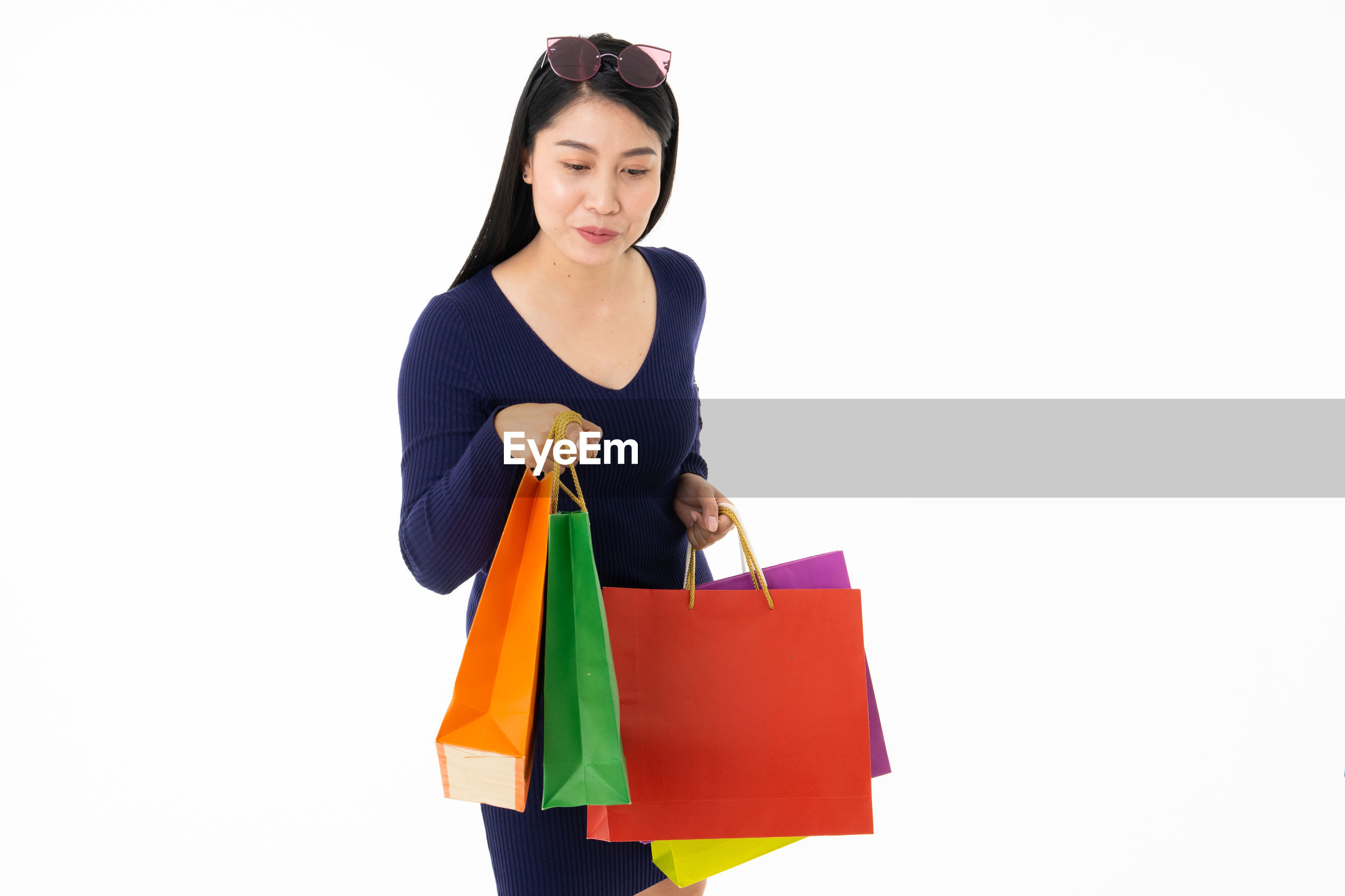 Young woman holding shopping bags while standing against white background