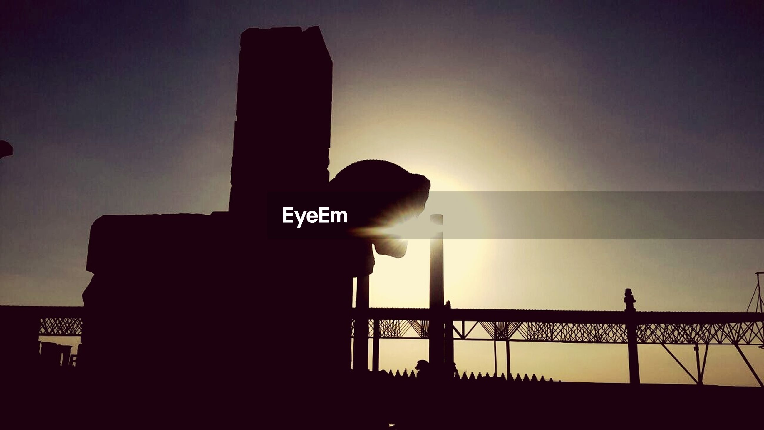 silhouette, built structure, sunset, architecture, low angle view, building exterior, sky, sun, clear sky, copy space, street light, dusk, outline, city, outdoors, building, sunlight, no people, dark, tower