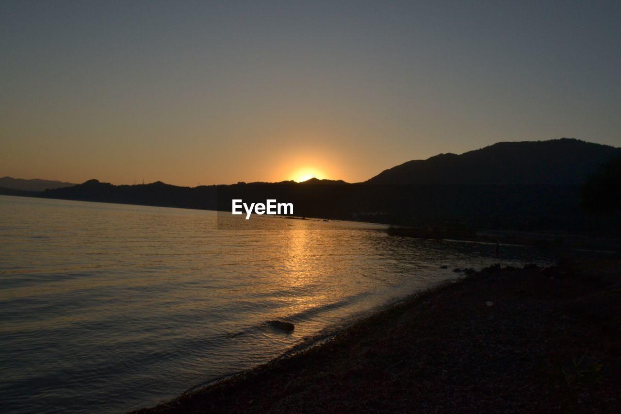 sky, sunset, water, tranquility, tranquil scene, scenics - nature, beauty in nature, silhouette, nature, mountain, no people, land, beach, sea, idyllic, orange color, non-urban scene, sunlight, sun, outdoors