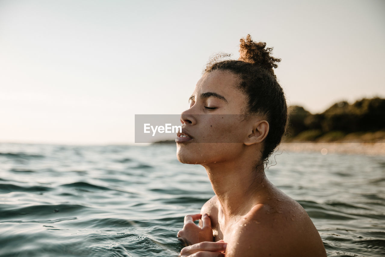 Close-Up Of Shirtless Young Woman Swimming In Sea
