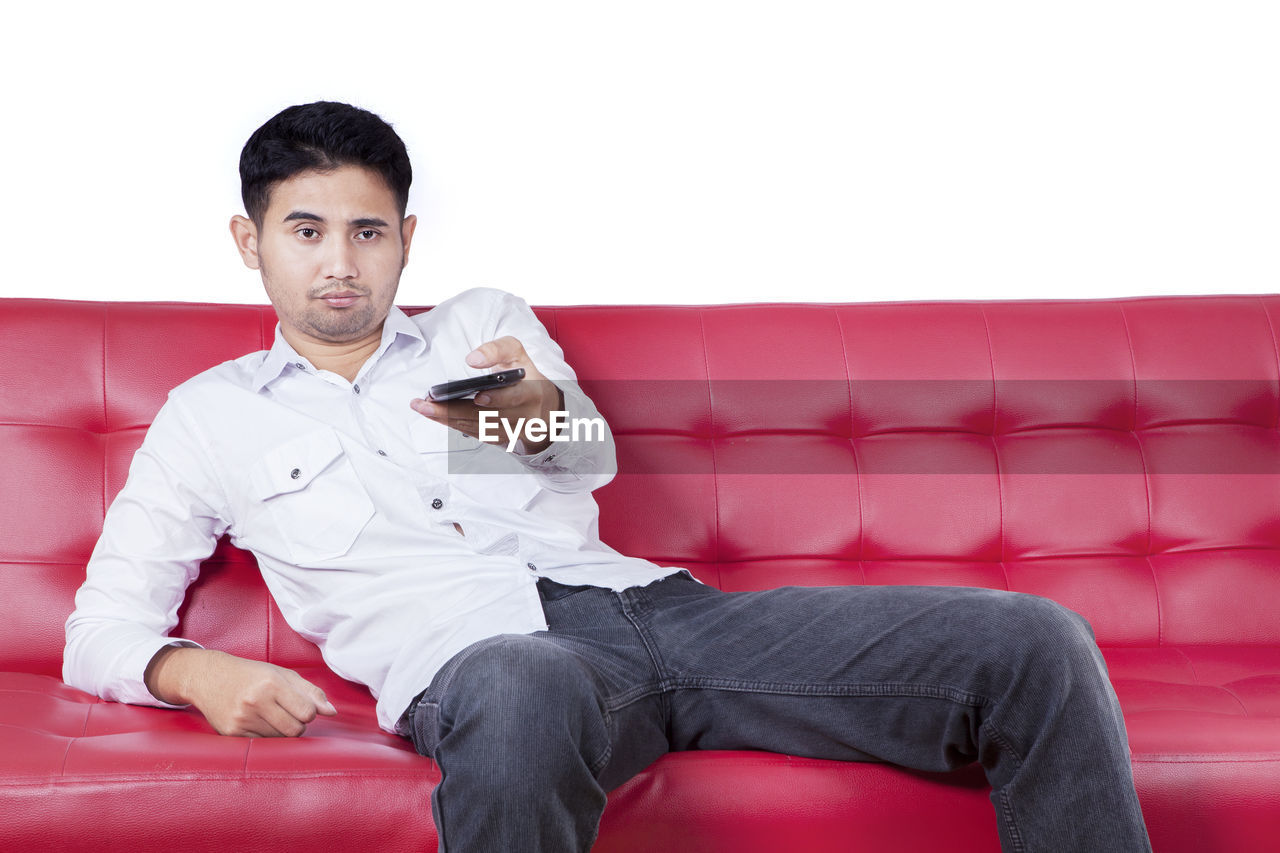 sitting, one person, young adult, front view, young men, sofa, looking at camera, seat, lifestyles, portrait, indoors, three quarter length, leisure activity, real people, relaxation, furniture, men, chair, armchair