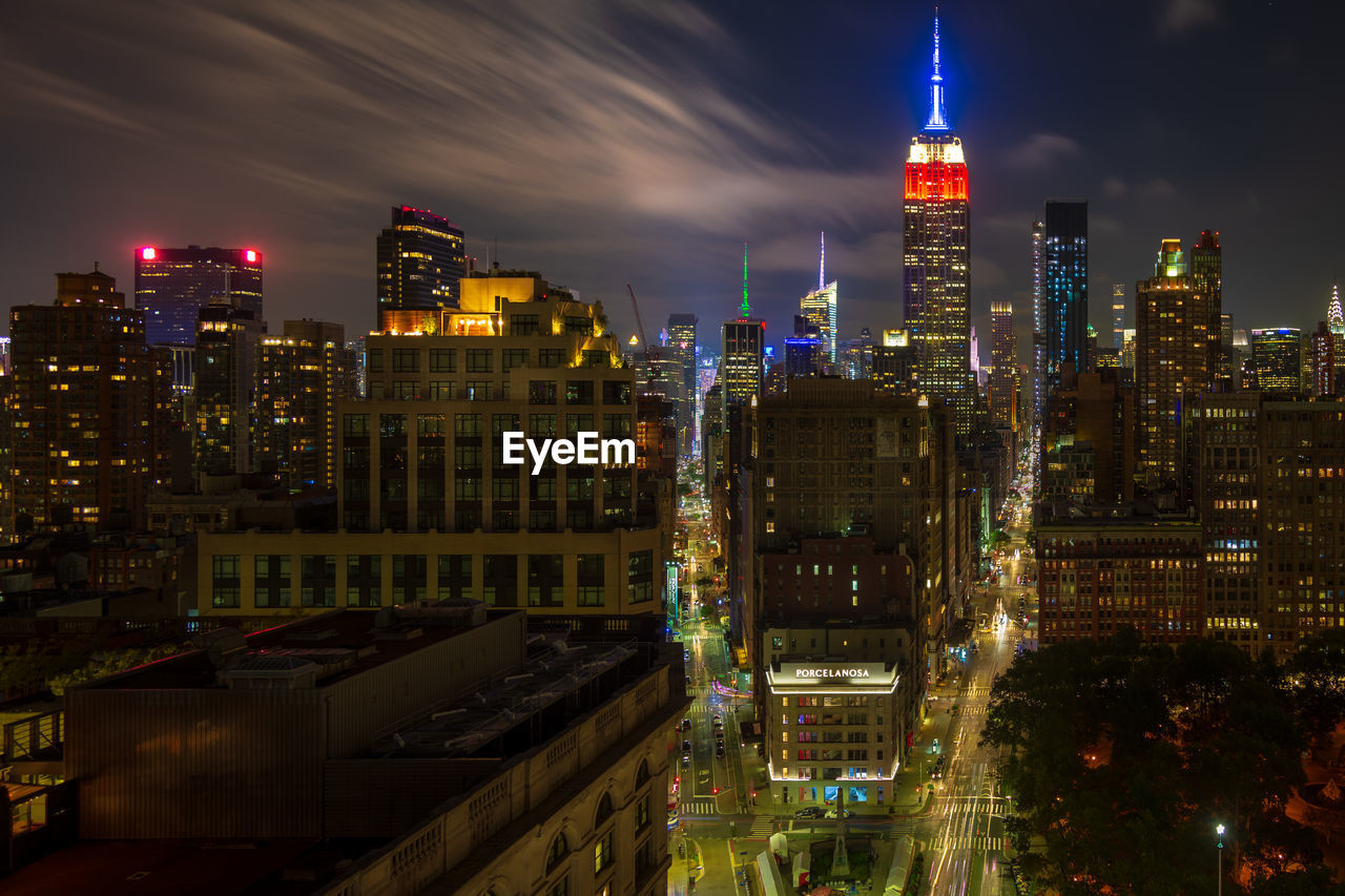 Illuminated empire state building amidst cityscape at night