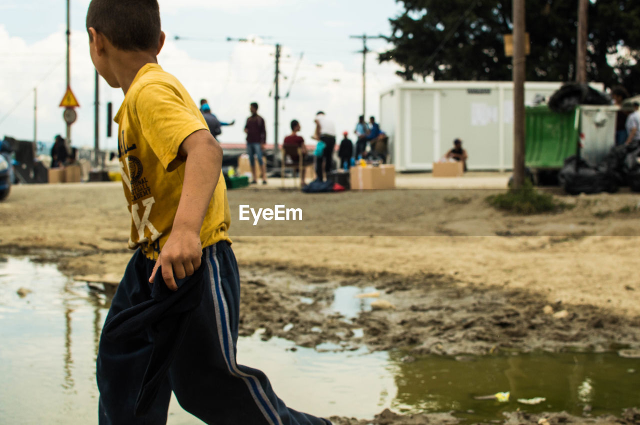Boy by puddle on street
