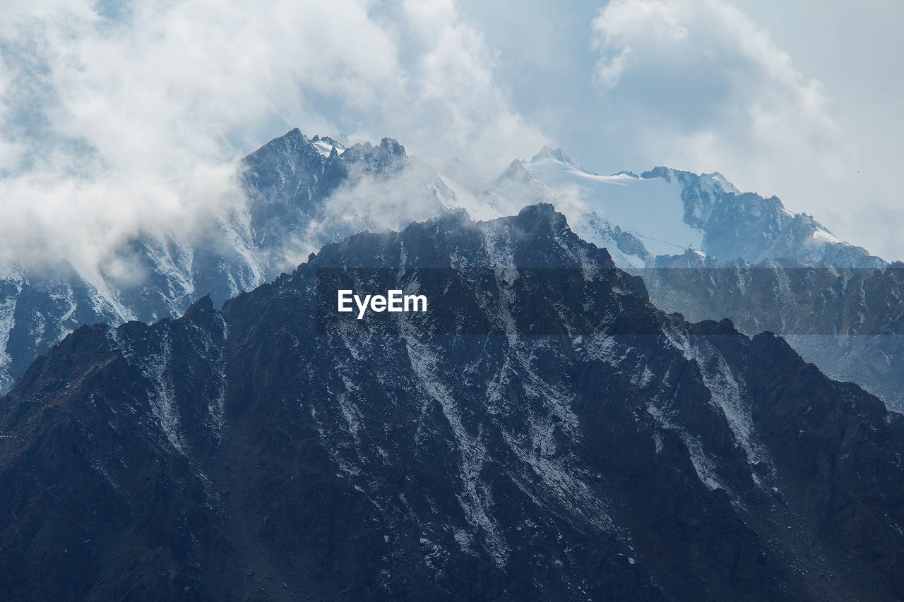 Snow-capped sharp mountain peaks in sunlight against the sky with clouds