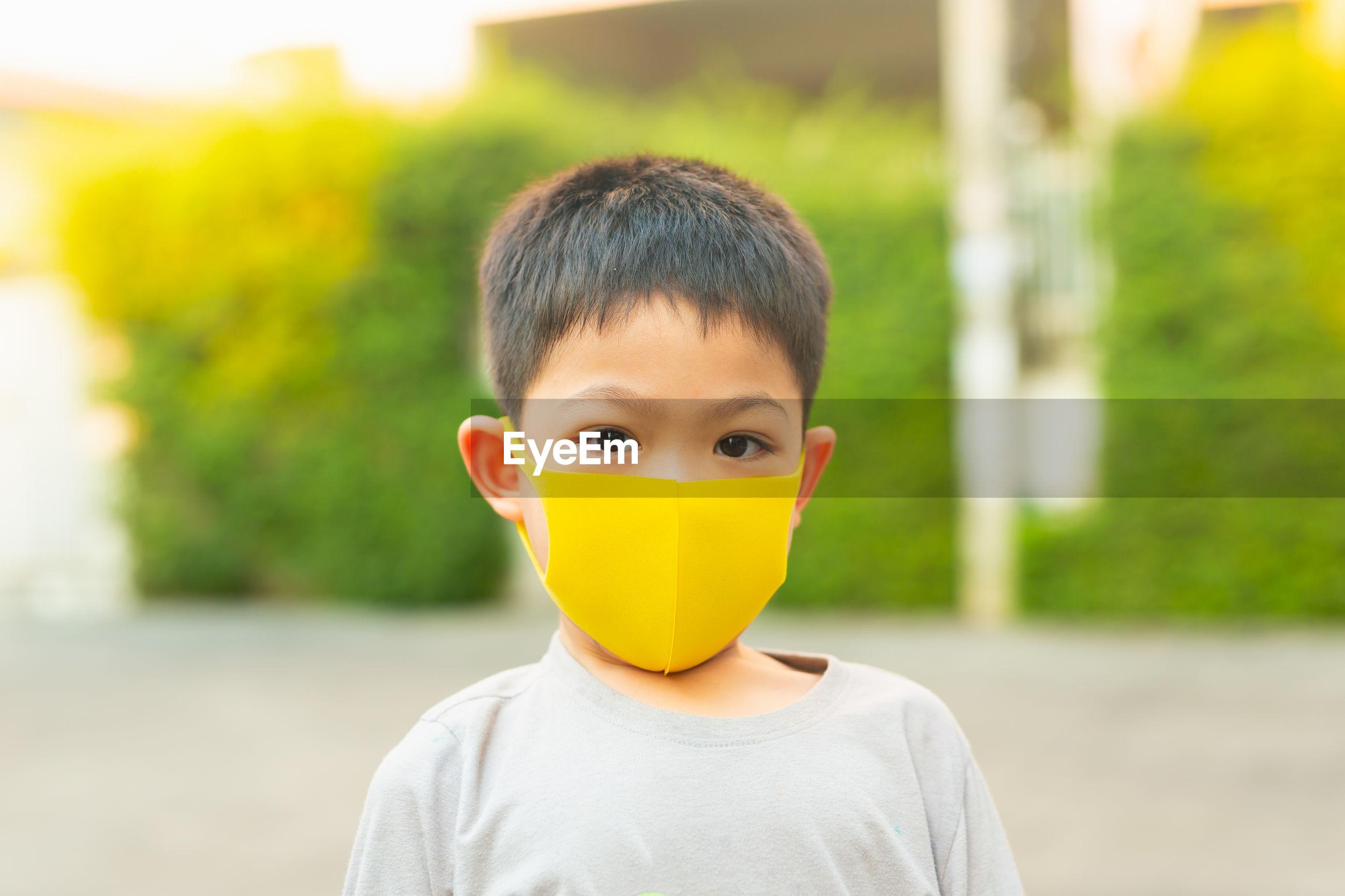 Close-up portrait of cute boy wearing mask