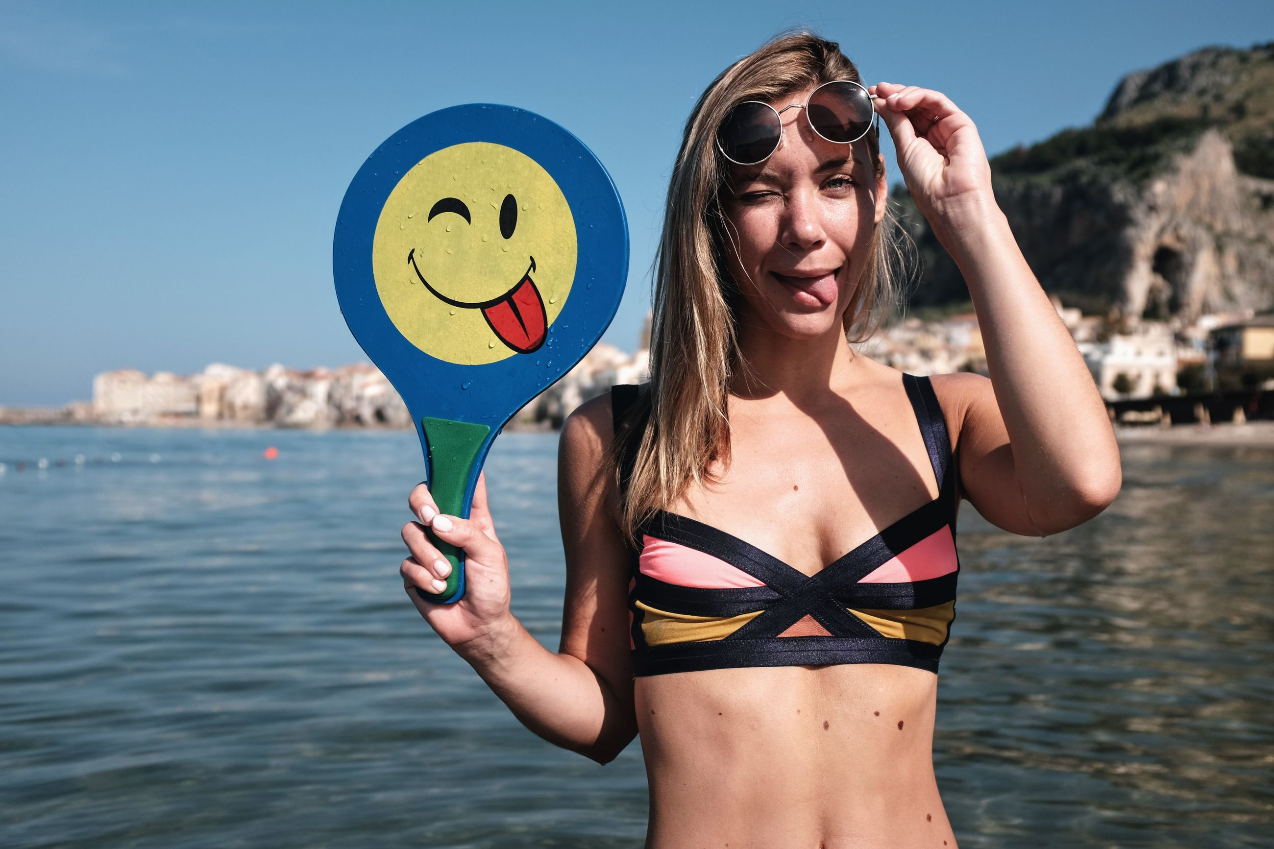 Portrait of young woman wearing bikini sticking out tongue in sea