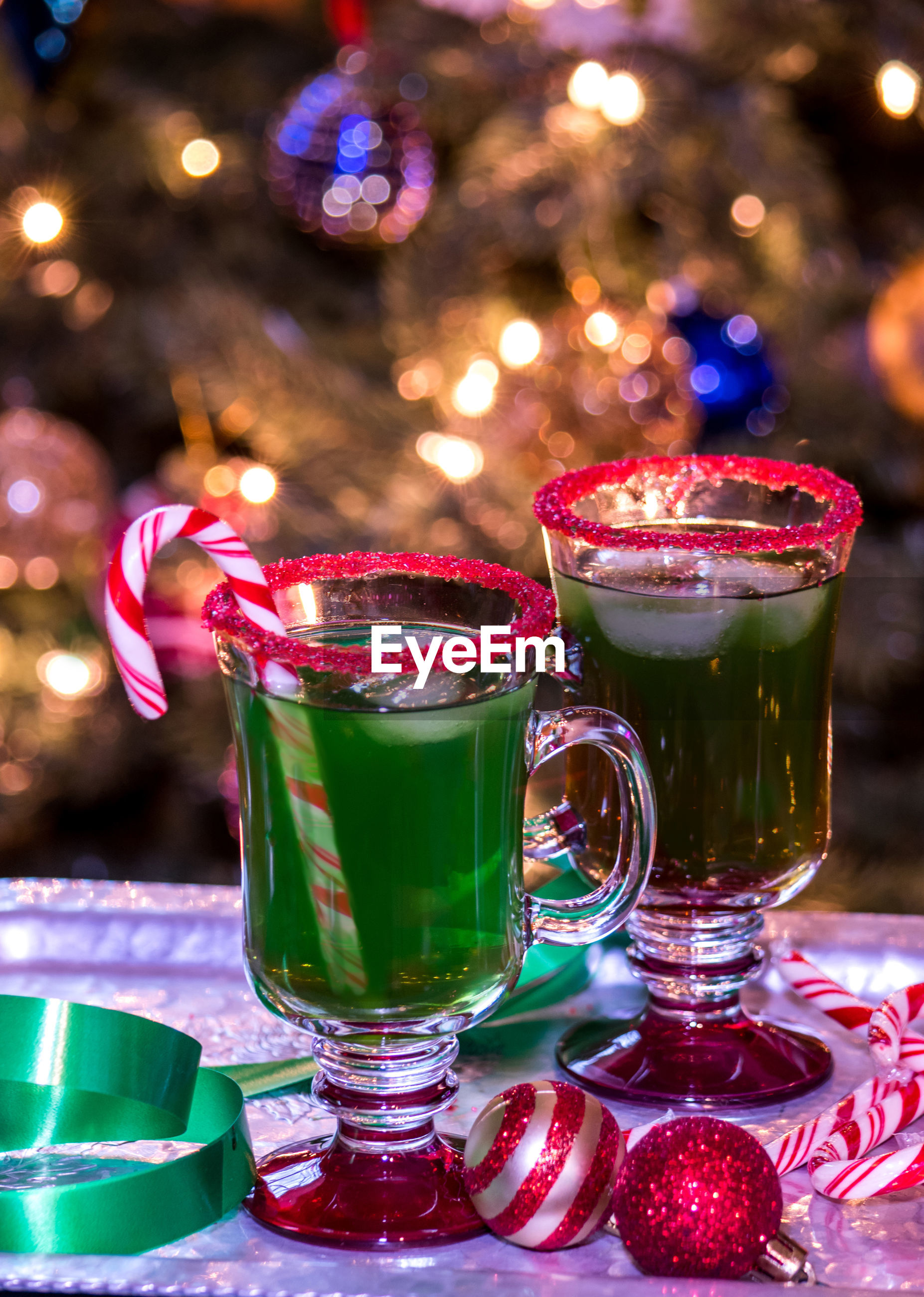 A green christmas punch for kids is garnished with a candy cane and red sugar rimmed glass.