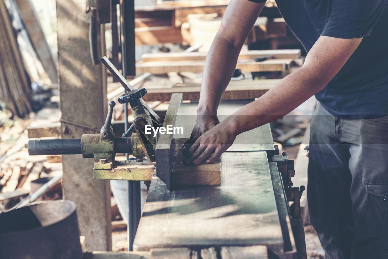 Carpenter cutting wood in workshop