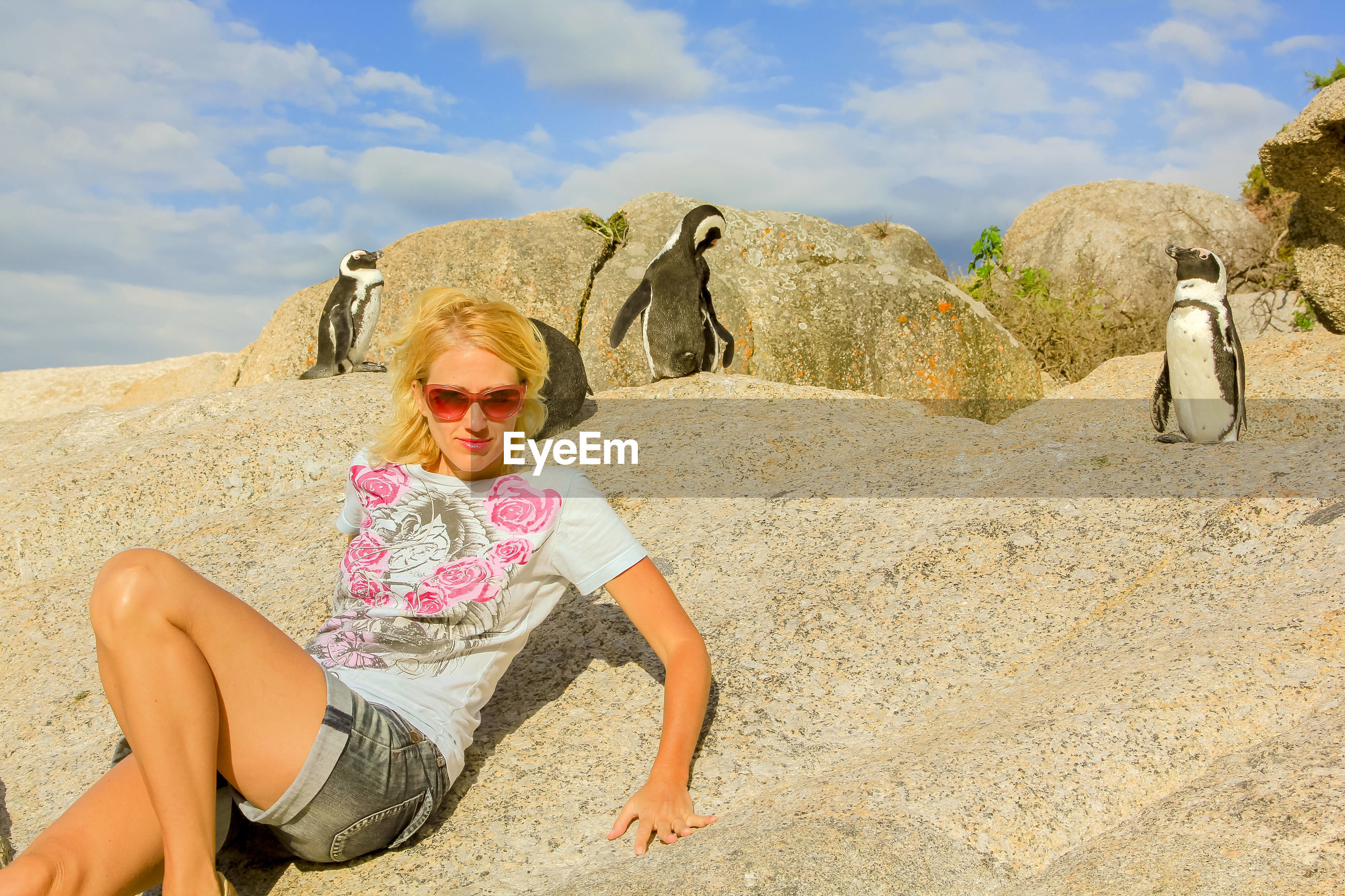 Portrait of woman on rock against penguins and sky
