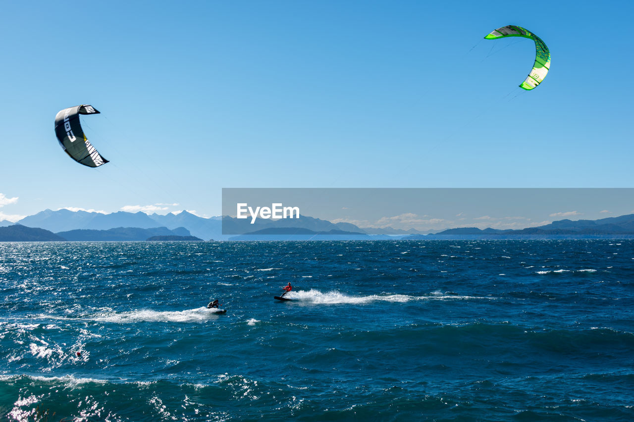 sport, adventure, extreme sports, water, sea, motion, sky, aquatic sport, unrecognizable person, nature, lifestyles, day, paragliding, mid-air, leisure activity, waterfront, flying, beauty in nature, parachute, kiteboarding, freedom, outdoors