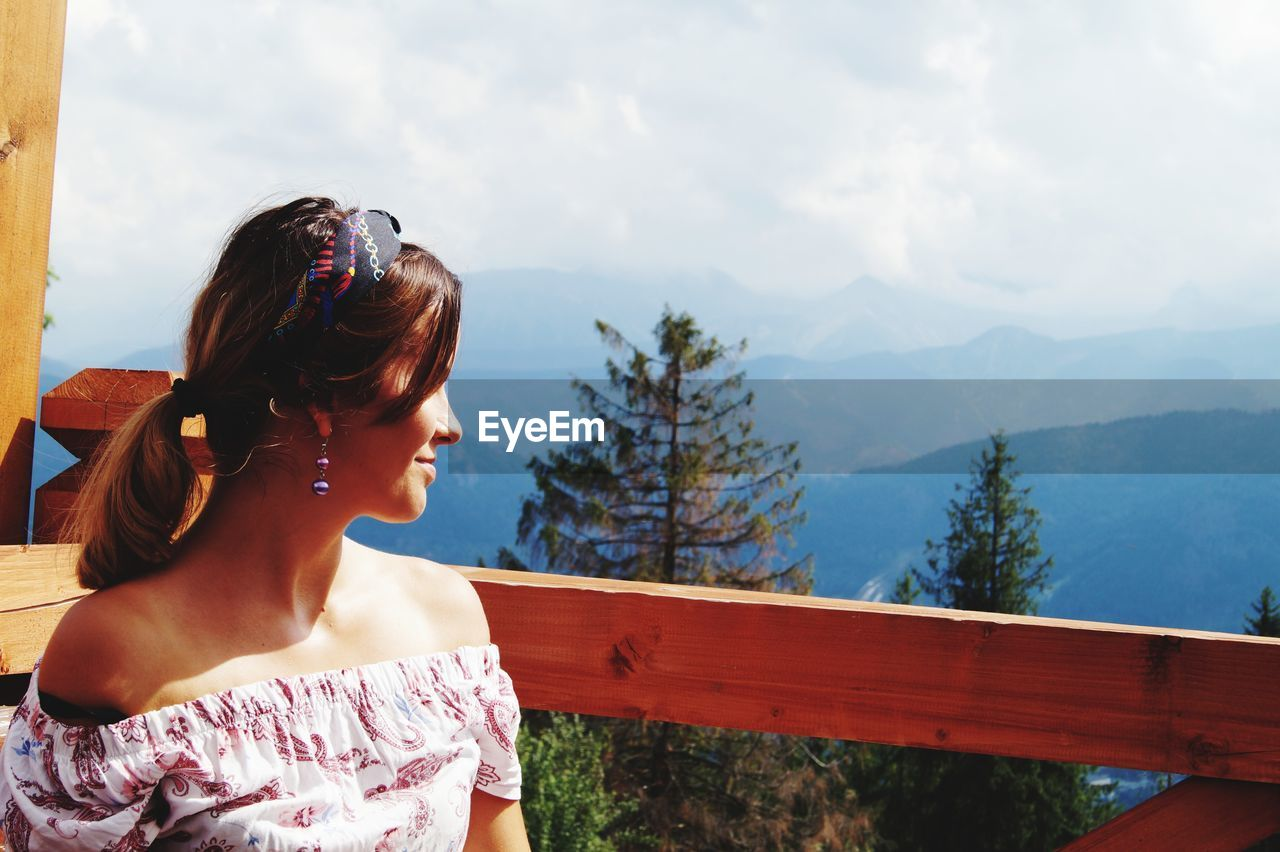 Smiling woman by railing against mountains and sky