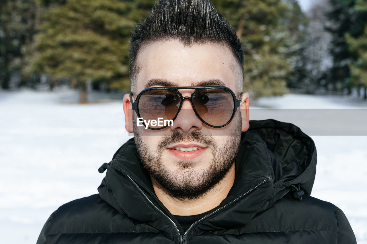 Portrait Of Young Man Wearing Sunglasses While Standing On Snow