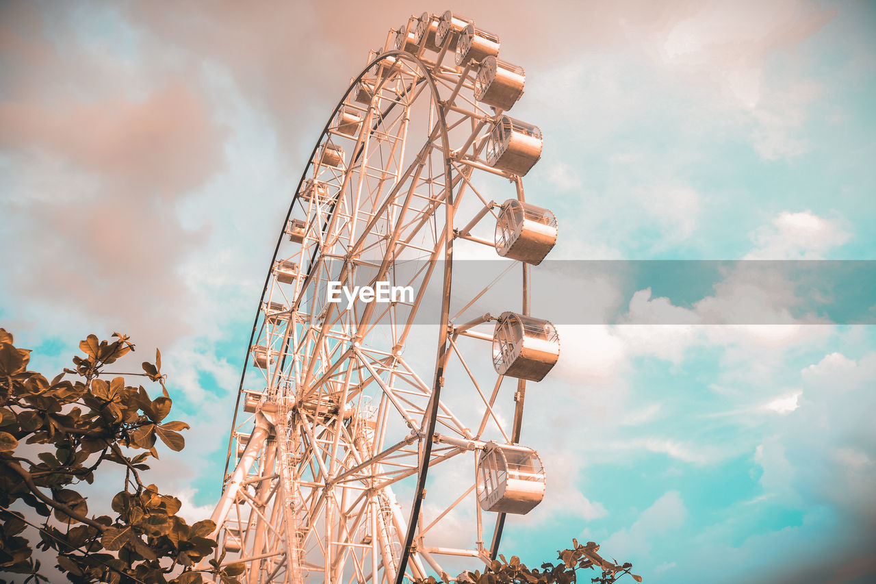 sky, low angle view, cloud - sky, amusement park ride, amusement park, arts culture and entertainment, nature, day, ferris wheel, no people, metal, outdoors, leisure activity, built structure, fairground, plant, blue, tree, architecture, fun, excitement