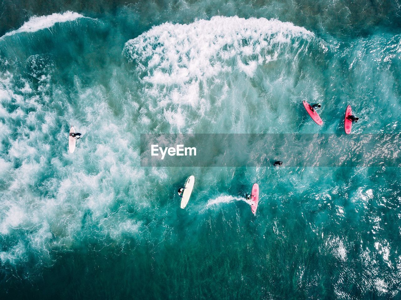 High Angle View Of People With Surf Board In Sea