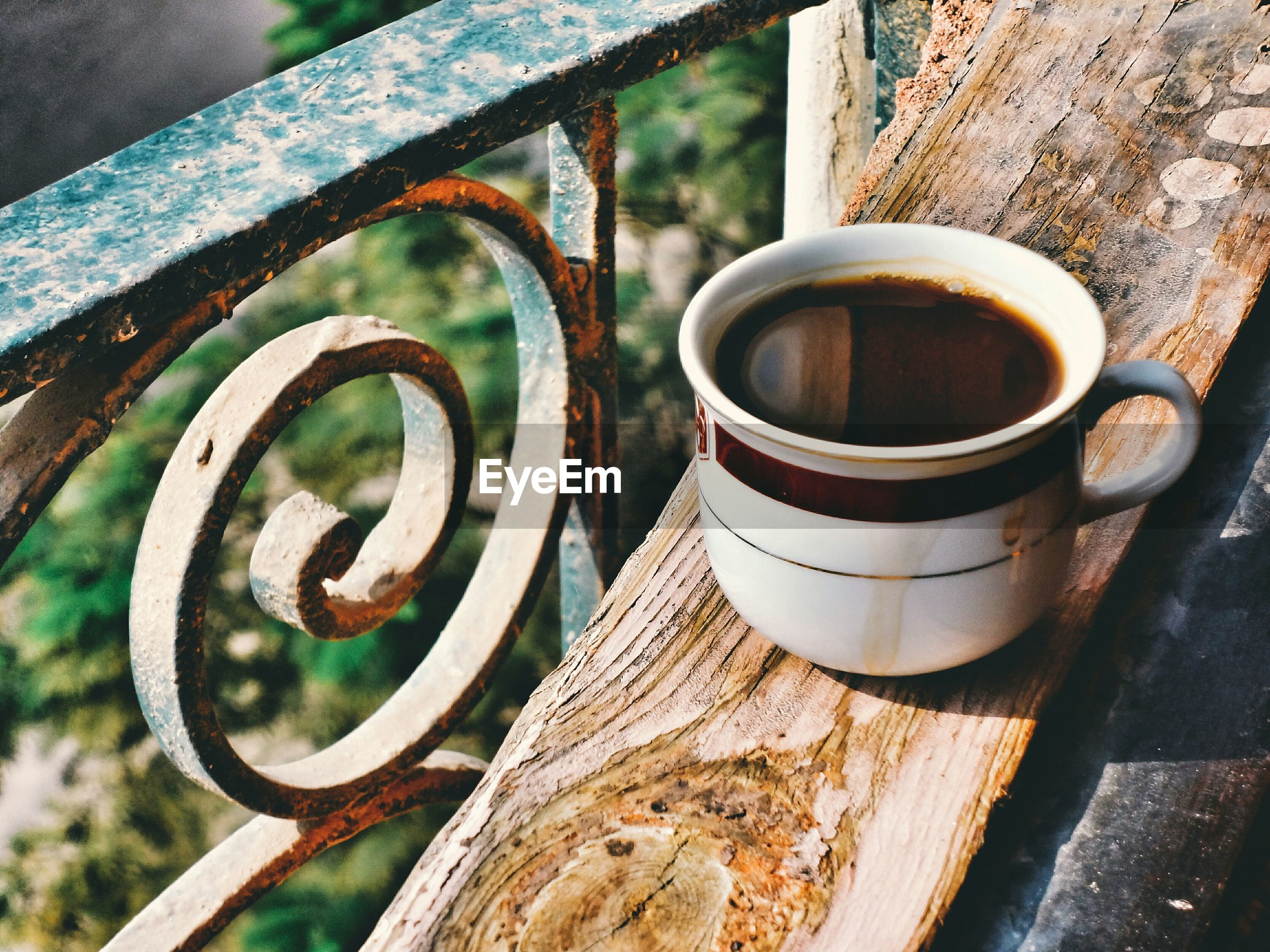 Close-up of black coffee on railing