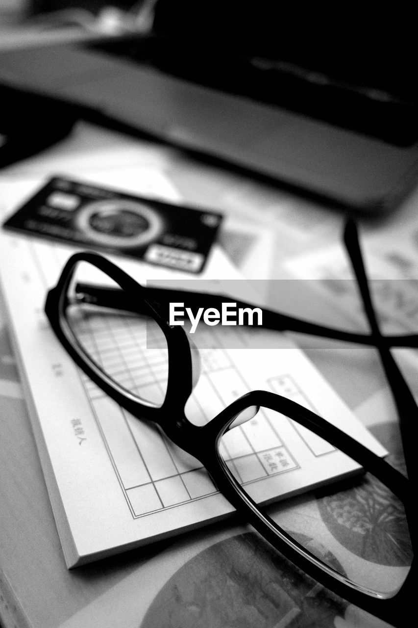 close-up, still life, glasses, eyeglasses, no people, indoors, table, paper, technology, selective focus, high angle view, communication, focus on foreground, magnifying glass, wireless technology, connection, text, portable information device, pen, personal accessory