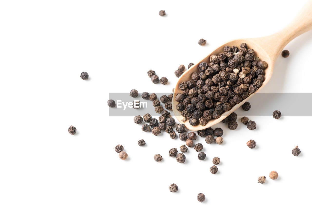 Close-Up Of Black Peppercorns In Wooden Spoon Over White Background