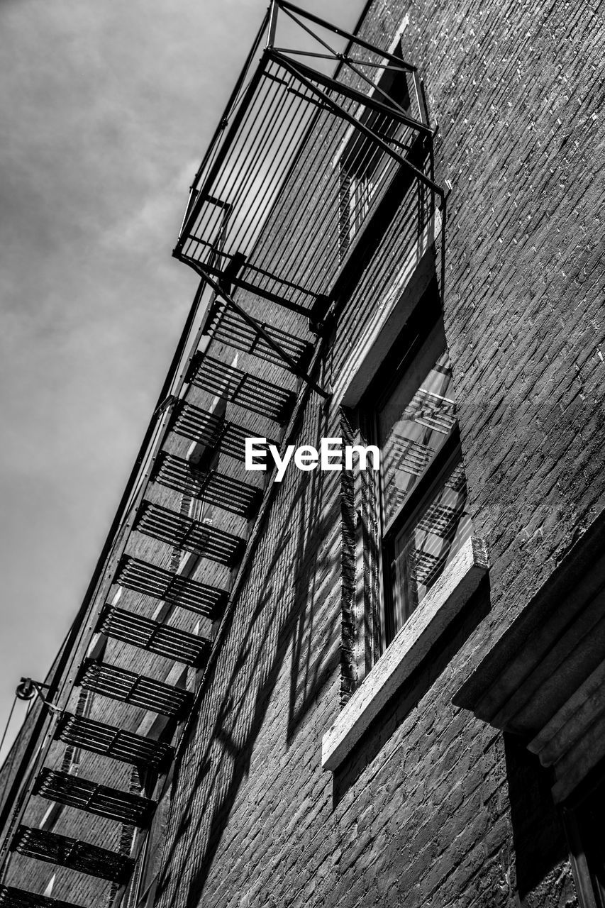 low angle view, built structure, architecture, building exterior, building, day, no people, sky, nature, outdoors, wood - material, wall, window, fire escape, cloud - sky, staircase, wall - building feature, residential district, tall - high, protection, apartment