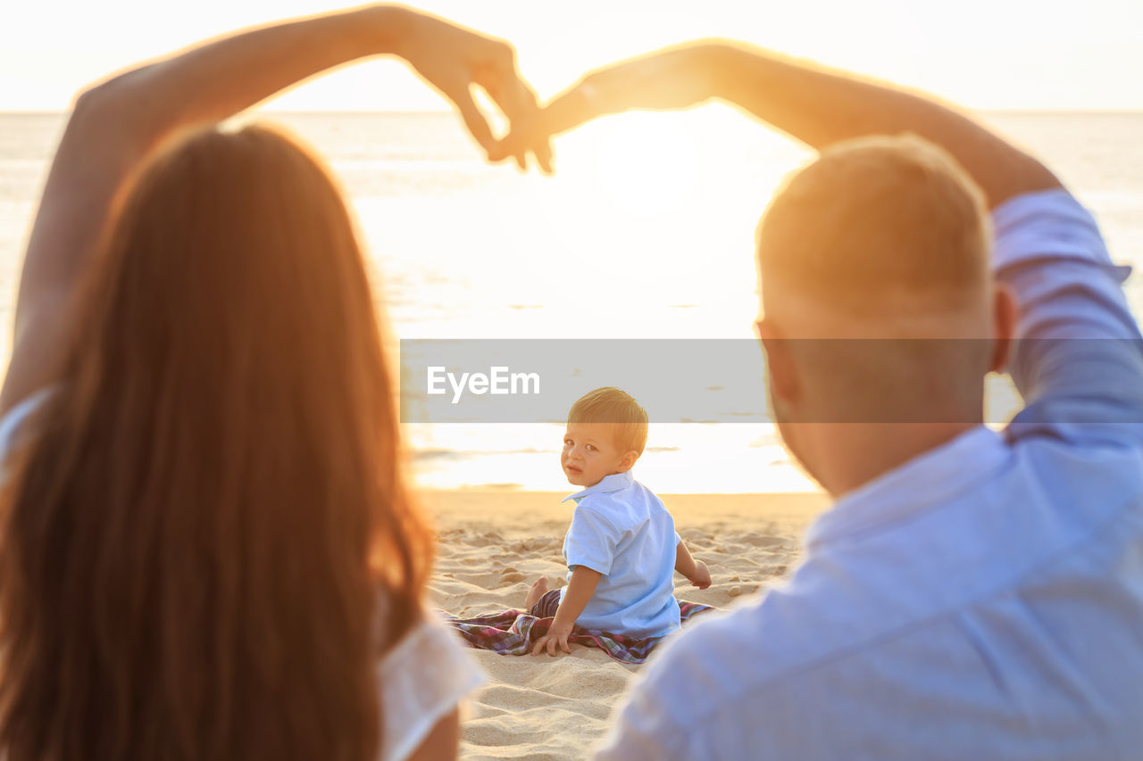 Rear view of parents making heart shape while son sitting at beach during sunset