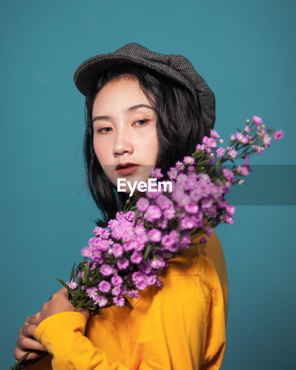 Portrait of beautiful young woman holding flowers against colored background