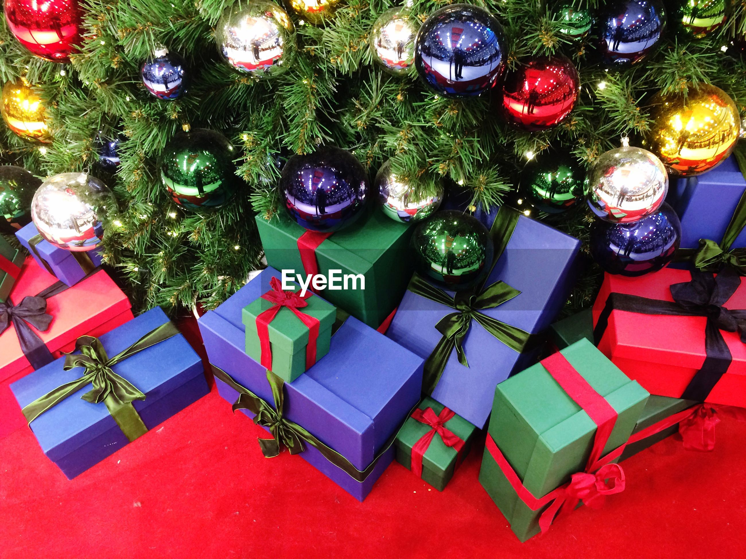 High angle view of christmas presents by tree