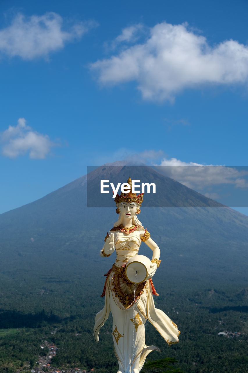 Statue against blue sky and volcano
