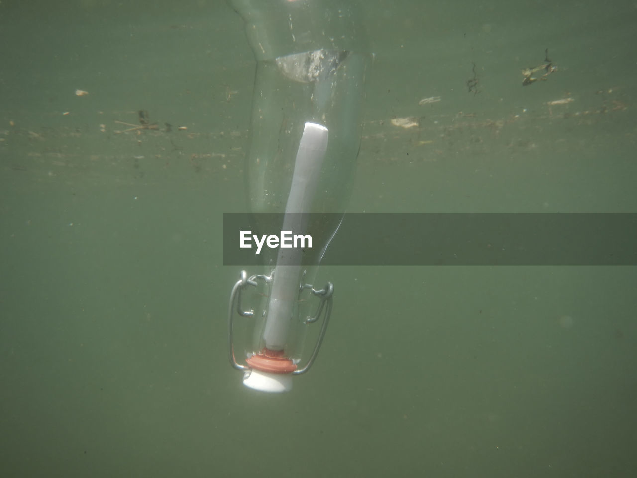 View Of Glass Bottle With Message Sinking In Water