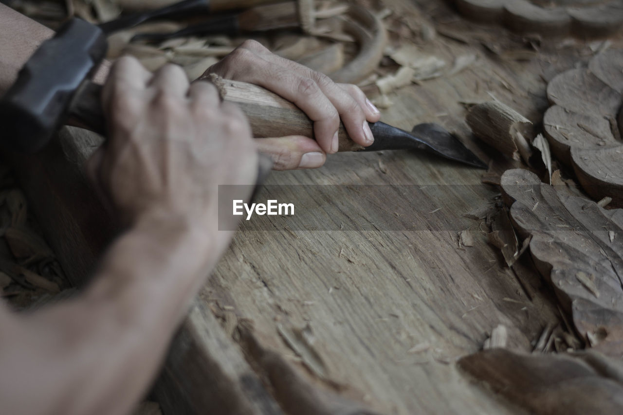 human hand, hand, real people, one person, human body part, wood - material, selective focus, holding, indoors, unrecognizable person, occupation, high angle view, working, skill, preparation, table, craft, lifestyles, cutting, finger